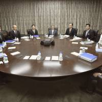Bank of Japan Gov. Haruhiko Kuroda (center) and the central bank's policymakers attend a meeting on Dec. 18 at its headquarters in Tokyo. | KYODO