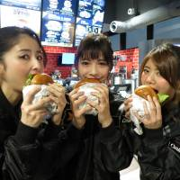 Models bite into Carl's Jr. burgers at the U.S. fast food chain's new outlet in Tokyo's Akihabara district on Wednesday. | KAZUAKI NAGATA