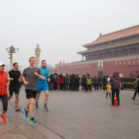 Facebook CEO Mark Zuckerberg (front right) runs past Tiananmen Gate, at the entrance to the Forbidden City, in Beijing on Friday. Facebook CEO Mark Zuckerberg took a mask-free jog through Beijing's Tiananmen Square, smiling through thick smog as he seeks greater access for his company to China, where its service is banned. | FACEBOOK / AFP-JIJI