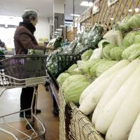 A customer shops for vegetables at a supermarket in Tokyo last month. | BLOOMBERG