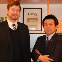 Akira Isshiki (right) and Gareth Monteath of Link Global Solution Inc., which offers intercultural communication training, pose at their office in Tokyo on March 14. | KYODO