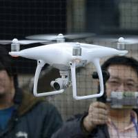 DJI staffers demonstrate the Phantom 4 in Tokyo on Thursday. DJI has its eyes on Japan, where enthusiasts spend vast sums on their photo and videography hobbies. | AP