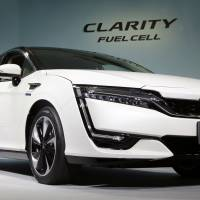 Honda Motor Co. President and Chief Executive Takahiro Hachigo unveils the Clarity at the automaker's headquarters in Tokyo on Thursday. The company is initially seeking to lease it to government and business users, and will sell it from next year. | AP