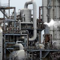 Steam rises from a stack at a petrochemical plant in the Shunan industrial complex in Shunan, Yamaguchi Prefecture. Business investment by Japanese firms in the October-December period rose 8.5 percent when compared to the previous year, but the outlook is dim, government sources said Tuesday. | BLOOMBERG