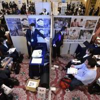 Companies brief job-seeking college students in small booths at a job fair in Tokyo Tuesday, the start of the job-hunting season for students graduating in March 2017. The selection process by companies, including interviews, will start on June 1. | KYODO