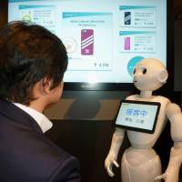 A SoftBank Pepper robot pitches cellphone items during a demonstration Tuesday in Chuo Ward, Tokyo. | KYODO