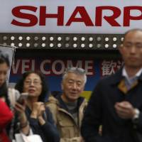The Sharp logo is seen above a group of Chinese tourists outside an electronics store in Tokyo on Wednesday. | REUTERS