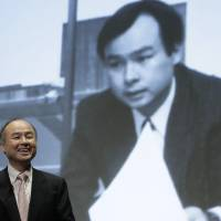 Masayoshi Son, chairman and chief executive officer of SoftBank Group Corp., smiles as a photo from his past is projected in the background at a news conference in Tokyo last month.   BLOOMBERG