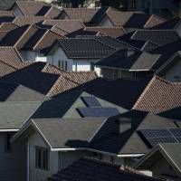 Two homes in this strip of tract housing in Inzai, Chiba Prefecture, have solar panels on their roofs. The solar-energy market is said to be shifting from mega-projects to rooftops because of the lack of large spaces in Japan. | BLOOMBERG