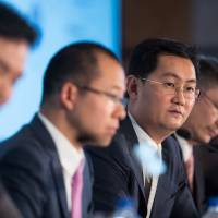 Ma Huateng (second from right), chairman and chief executive officer of Tencent Holdings, speaks during a news conference in Hong Kong last March. | BLOOMBERG