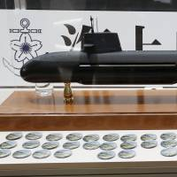 A visitor takes a picture of a model of a Maritime Self-Defense Force Soryu-class submarine at the MAST Asia 2015 defense exhibition and conference in Yokohama last May 13. | REUTERS