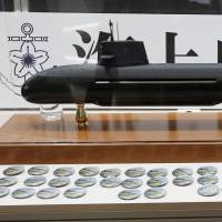 A visitor takes a picture of a model of Japan Maritime Self-Defense Forces diesel-electric submarine Soryu at the MAST Asia 2015, defense exhibition and conference in Yokohama in May 2015. | REUTERS
