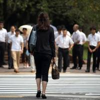 A woman waits to cross a road in the Tokyo's Kasumigaseki area, which is the center of Japan's government agencies. Although the government aims to increase the ratio of women in supervisory positions, they fill just 6.2 percent of junior management jobs in the bureaucracy. | BLOOMBERG