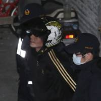 The suspect in the decapitating a 4-year-old girl is escorted to a detention center in Taipei on Tuesday. | REUTERS