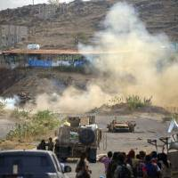 Yemeni fighters loyal to Yemen's Saudi-backed President Abed Rabbo Mansour Hadi, hold a position during clashes with Shiite Houthi rebels west of the city of Taiz on Monday. | AFP-JIJI