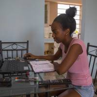 Yolanda Mauri works on her laptop at her home in Havana Saturday. For Mauri and hundreds of thousands of black Cubans, Barack Obama isn't just the first U.S. leader to visit their country in nearly nine decades. He's a black man whose rise to the world's most powerful job is a source of pride and inspiration. | AP