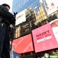 New York Police Department officers stand guard in Times Square on Tuesday. New York and Washington stepped up security in the wake of the attacks in Brussels, deploying counterterrorism reinforcements and the National Guard to airports and stations, officials said. | AFP-JIJI
