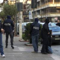 Italian Police arrest a man, kneeled at right, Saturday in the southern city of Bellizzi, near Salerno, Italy. Police identified the man detained as Djamal Eddine Ouali, an Algerian wanted in Belgium for facilitating illegal migration linked to the recent terror attacks in Paris. According to police he was sought under a European arrest warrant for alleged involvement in a network in Brussels that makes false documents, including those used by extremists implicated in the Paris and Brussels attacks. | CARMINE CAPPETTI / WWW.ASALERNO.IT VIA AP