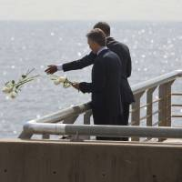 President Barack Obama and Argentine President Mauricio Macri toss roses into the river during their visit to Parque de la Memoria (Remembrance Park) in Buenos Aires Thursday. Obama visited the memorial to victims of the country's murderous U.S.-backed dictatorship who were killed or went missing from 1976-1983. | AP