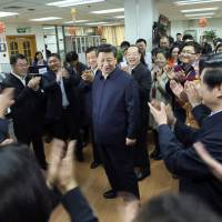 People applaud as Chinese President Xi Jinping visits the newsroom of the People's Daily in Beijing on Feb. 19. | AP