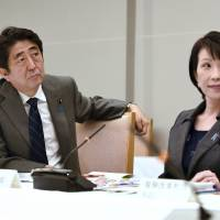 Prime Minister Shinzo Abe and Internal Affairs and Communications Minister Sanae Takaichi listen to Nagoya University professor and Nobel Prize winner Hiroshi Amano at Abe's official residence in Tokyo in October 2014. | AP