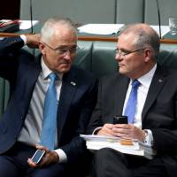 Australian Prime Minister Malcolm Turnbull (left) speaks with Australian Treasurer Scott Morrison during Question Time in the House of Representatives at Parliament House in Canberra, Australia, Thursday. | REUTERS