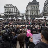 People observe a minute of silence for Tuesday's bombing victims at the Place de la Bourse in central Brussels on Thursday. | AP