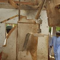 People inspect a damaged mosque following a suicide bomb explosion in Maiduguri, Nigeria, Wednesday. | AP