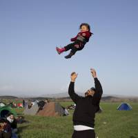 A Syrian man plays with his 1-year-old child as refugees and migrants wait to be allowed to cross the border to Macedonia in the northern Greek border station of Idomeni on Tuesday. | AP