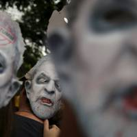 Demonstrators wear masks depicting former Brazilian President Luiz Inacio Lula da Silva during a protest against the current leader, Dilma Rousseff, in Sao Paulo, on Sunday.   REUTERS