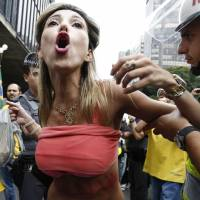 A demonstrator is held by police after she turned up her shirt during a protest to demand the resignation of Brazilian President Dilma Rousseff on Sunday in Sao Paulo.   AFP-JIJI