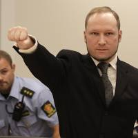 Norwegian mass murderer Anders Behring Breivik makes a clenched fist salute after arriving at an Oslo court in August 2012. | AP