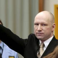 Mass killer Anders Behring Breivik raises his arm in a Nazi salute as he enters the court room in Norway's Skien prison on Monday. | REUTERS