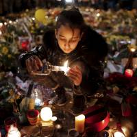 A girl lights candles Saturday at the Place de la Bourse in Brussels as people pay tribute to the victims of Tuesday's bomb attacks in Belgium. | REUTERS
