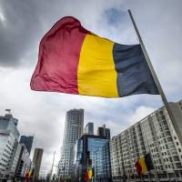 The Belgian flag flies at half-staff Wednesday at the Hofplein in Rotterdam, one day after some 35 people were killed in bombings at Zaventem Airport and on a metro train. | LEX VAN LIESHOUT / ANP / AFP-JIJI