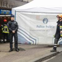 Police stand guard as rescuers enter the Maelbeek — Maalbeek metro station in Brussels on Wednesday, a day after the station and the Brussels-Zaventem airport were attacked by triple blasts that killed some 30 people and left around 250 injured. Belgian prosecutors said two brothers carried out suicide attacks at Brussels airport and on a metro train, with one of them leaving a desperate will in a trash can saying he did not know what to do any more. | THIERRY ROGRE / BELGA / AFP-JIJI