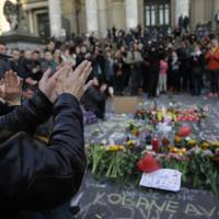 People applaud in tribute to victims at a makeshift memorial in front of the stock exchange at the Place de la Bourse (Beursplein) in Brussels on Tuesday following triple bomb attacks in the Belgian capital that killed about 35 people and left more than 200 people wounded. | AFP-JIJI