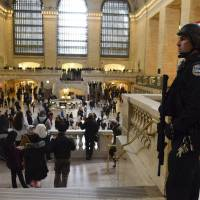 A member of the NYPD Joint Terrorism Task Force patrols Grand Central Station in  New York on Tuesday. | REUTERS