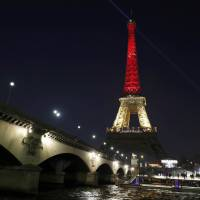 The Eiffel Tower is illuminated Tuesday evening with the colours of the Belgian flag in tribute to the victims of the Brussels bomb attacks.