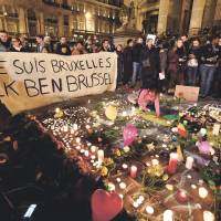 "People mourn for the victims of the triple terrorist bombings in Belgium at Place de la Bourse in the center of Brussels on Tuesday. The banner alongside flowers, candles and messages of peace reads, ""I am Brussels"" in French and Dutch.  