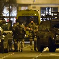 Special operations police take positions during a raid in Brussels on Tuesday. Belgian police launched an anti-terror raid linked to last year's Paris attacks in a Brussels neighborhood on Tuesday. | AP