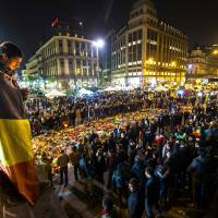 A man wrapped in a Belgian flag holds a candle as people gather at a makeshift memorial in front of Brussel's Stock Exchange on Place de la Bourse (Beursplein) on Thursday, two days after a triple bomb attack, claimed by the Islamic State group, hit Brussels' airport and the Maelbeek metro station, killing 31 people and wounding 300 others. | AFP-JIJI | AFP-JIJI
