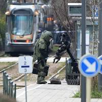 A bomb squad unit member stands next to a robot while examining a suspicious bag at a tram station in the Schaerbeek suburb of Brussels on Friday after Belgian police arrested a suspect in a fresh anti-terrorist operation. | AFP-JIJI