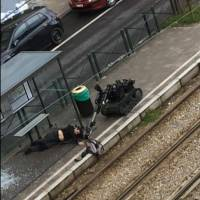 A bomb disposal robot approaches an injured man laying on the floor at a tram stop in Brussels on Friday in this image made from video. | AP