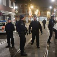 Belgian police stand in position on the site where shots were fired in the southern Forest district of Brussels on Tuesday. | AFP-JIJI