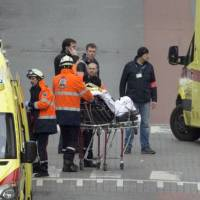 Emergency services evacuate a victim by stretcher after a explosion in a main metro station in Brussels rocked the Brussels airport and the subway system on Tuesday, killing at least 13 people and injuring many others. | AP