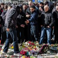 Right-wing demonstrators protest at a memorial site at the Place de la Bourse in Brussels Sunday. In a sign of the tensions in the Belgian capital and the way security services are stretched across the country, Belgium's interior minister appealed to residents not to march Sunday in Brussels in solidarity with the victims. | AP