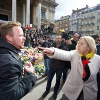 A woman and a man argue outside the stock exchange in Brussels on Sunday as tensions mounted after the square, which has become an unofficial shrine to victims of the March 22, terror attacks, was invaded by some 200 far-right football hooligans. | NICOLAS MAETERLINCK / BELGA / AFP-JIJI