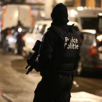 Police officers take part in an operation in the Brussels district of Schaerbeek late Thursday. Schaerbeek is where the three airport attackers departed from on Tuesday morning carrying three explosive-packed suitcases. | AFP-JIJI