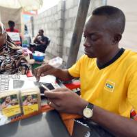An employee of mobile phone operator MTN tries to register a client with the network in the Obalende district of Lagos on Tueday. South African mobile phone operator MTN fueled the Boko Haram insurgency in northeast Nigeria by failing to disconnect millions of unregistered users, Nigerian President Muhammadu Buhari said. | AFP-JIJI